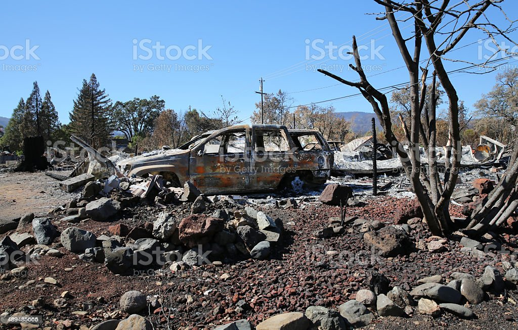 Fire damaged car and burned down home stock photo