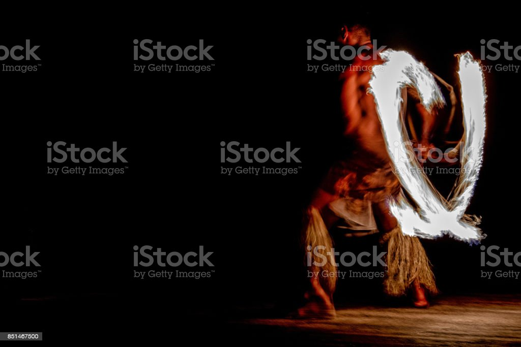 Fire dance Cook Islands polynesian dancer with pole of flames stock photo