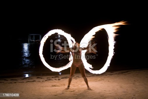 Woman dancing with fire circles.  Intentional motion blur.