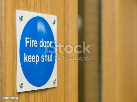 A fire door sign, screwed into a fire door