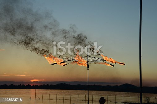 silhouettes of fire eaters at lake during sunset