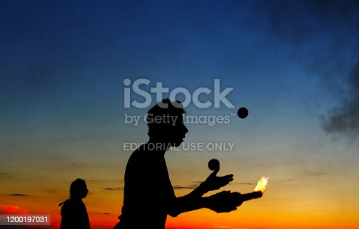 Lindau, Germany, 05/27/2013 silhouettes of fire eaters at lake during sunset