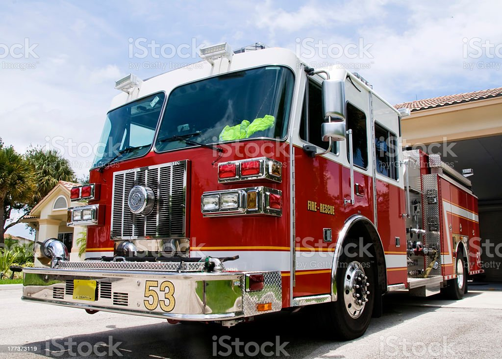 A large fire engine sits in front of the station house ready for an...
