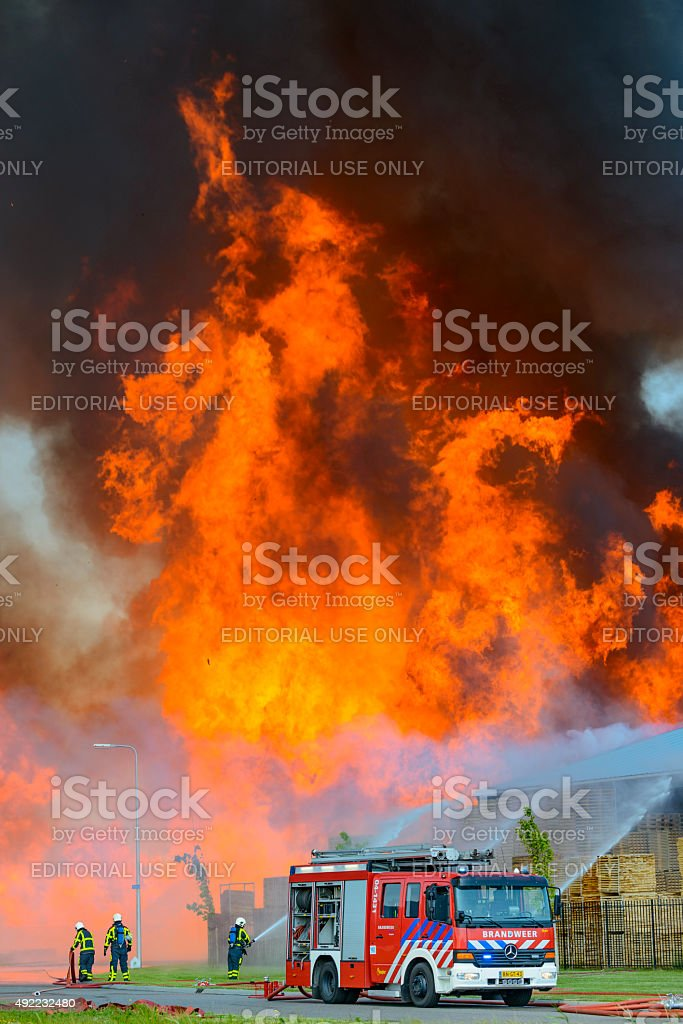 Fire engine in front of a fire in a pallet factory in an industrial...