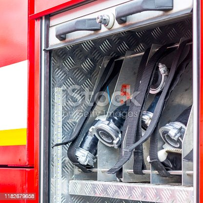 istock Fire engine, side view, neatly folded equipment inside the fire engine. 1182679658