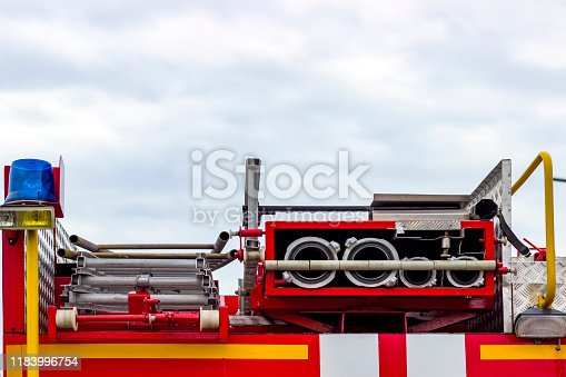 istock Fire engine, side view, neatly folded equipment inside the fire engine. 1183996754