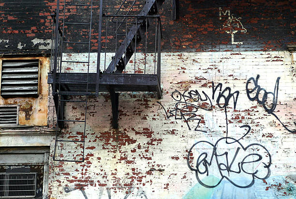 fire escape on side of old building with grafitti stock photo