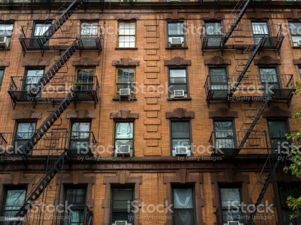 Fire Escapes in New York City View of fire escape outside red brick New York apartment Air Conditioner Stock Photo