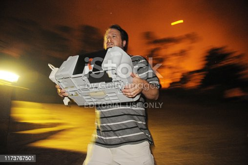 Paarl, South Africa.  5 March 2009.  In the street with flames behind him, Marius van Tonder rescues his printer as he evacuated his Paarl home.