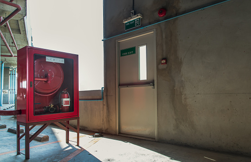 Fire exit door or Fire escape door with exit sign and Red fire fighting equipment cabinet in a car parking building.