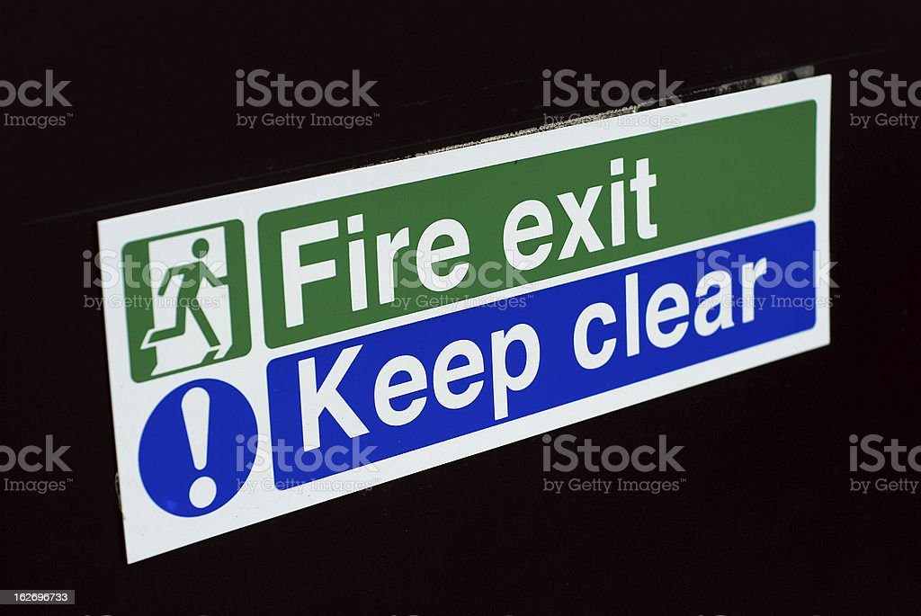 Fire exit keep clear sign on black door royalty-free stock photo