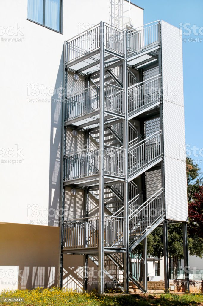 Fire Exit. Metal fire escape outside ladder on modern apartment building for emergency. Fire stairs on the building. A staircase on the external wall of an urban building. stock photo