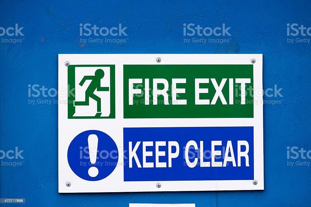 Fire exit sign at blue metal door stock photo