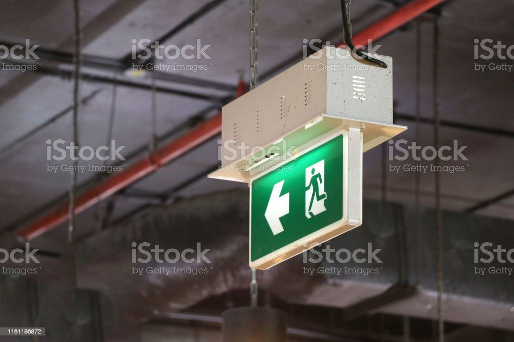 Fire exit sign hanging on top of the building. Fire exit sign...