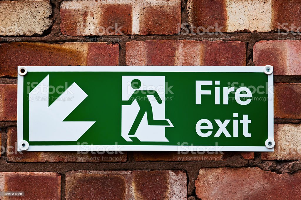 Fire exit sign on the red clay brick wall stock photo