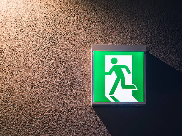 fire exit sign on wall building safety signage - exit sign stock photos and pictures