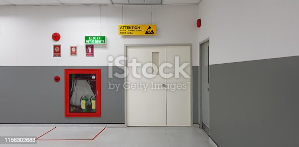 istock Fire exit way door and fire exit sign lightbox and fire hose in electronic industry ,Green emergency exit sign door direction in case of emergency signage,Fire safety symbol and fire protection. 1156302683