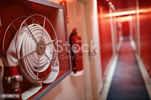 istock Fire extinguisher and hose reel in hotel corridor 621362710