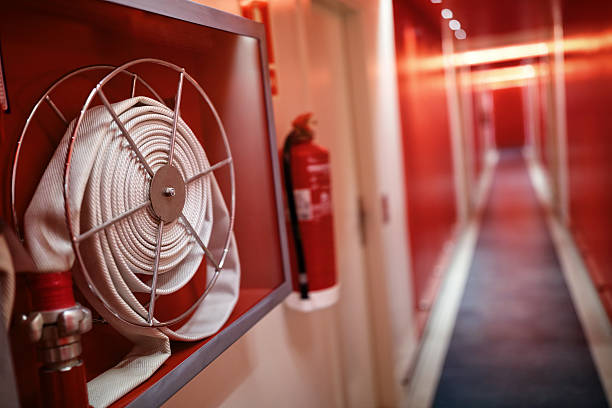 Fire extinguisher and hose reel in hotel corridor Fire extinguisher and fire hose reel in hotel corridor fire hydrant stock pictures, royalty-free photos & images