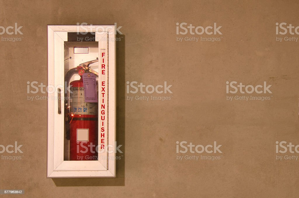 Fire extinguisher in a wall mounted glass case stock photo