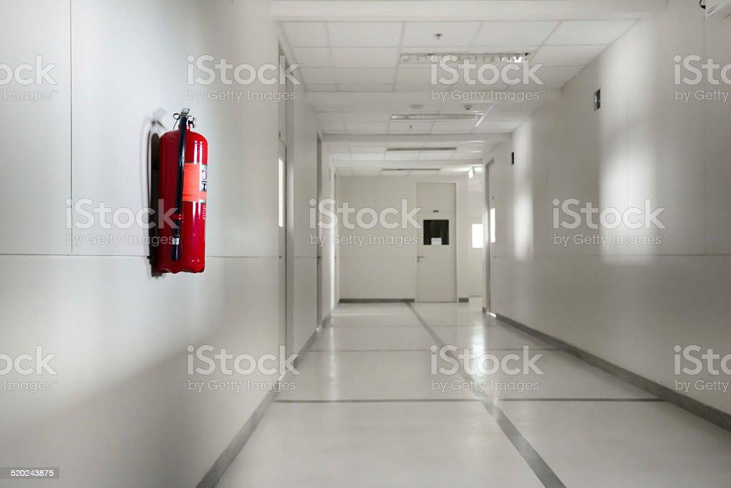 Fire extinguisher in empty white corridor stock photo