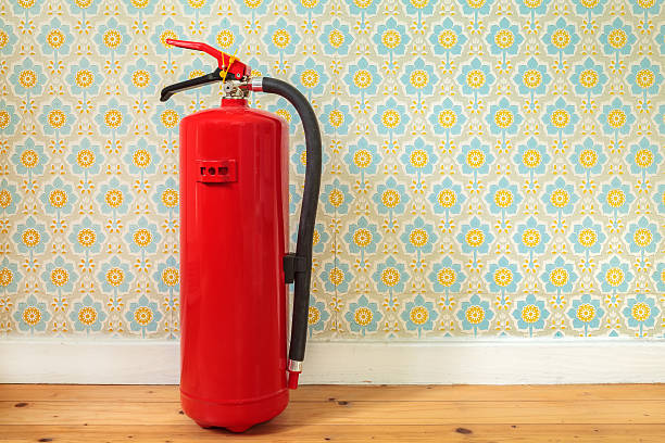 Fire extinguisher in front of retro flower wallpaper stock photo