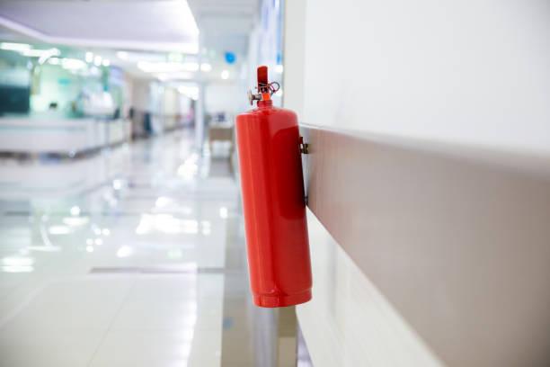 Extintor de incendios en el Departamento de operaciones. Instale un extintor de incendios en la pared del edificio. Extintor de polvo químico seco en el pasillo - foto de stock