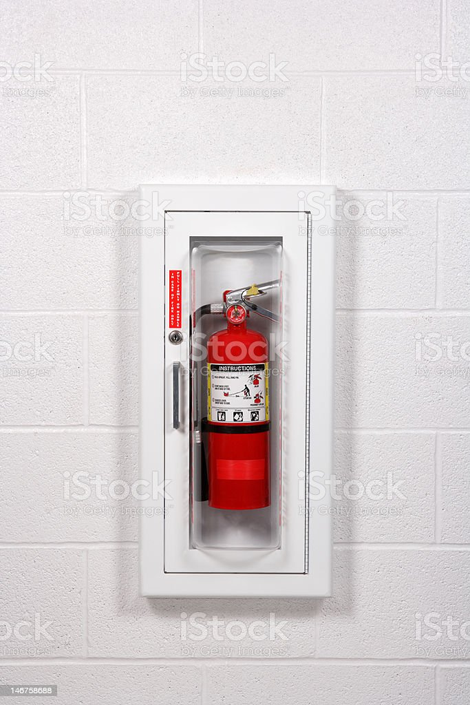 Fire Extinguisher in White Cabinet on Block Wall stock photo