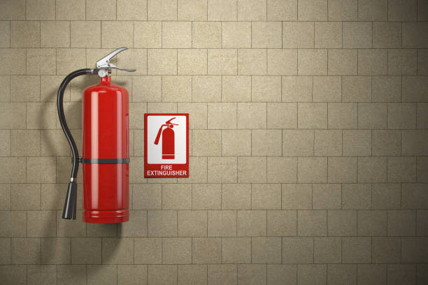 Fire extinguisher with emergency fire sign on the wall background. stock photo
