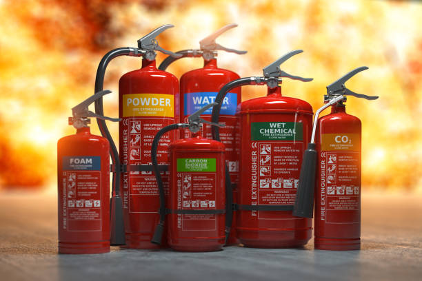 Fire extinguishers on a fire background. Various types and different sizes of extinguishers. 3d illustration stock photo