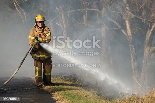 1195174769istockphoto Fire fighter spraying water on a bush fire in an suburban area of Knox City in Melbourne east. 950295514