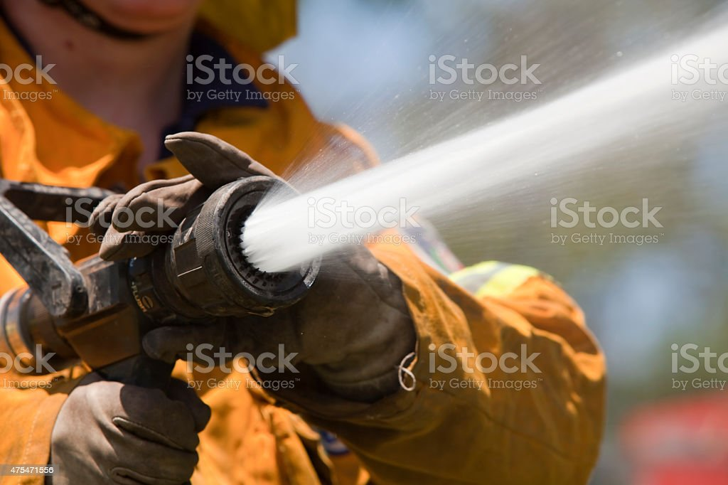 Fire fighter with hose stock photo