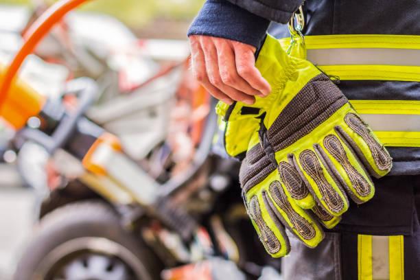 fire-fighter arbeitet mit professionellen werkzeugen auf ein abgestürztes auto - feuerwehrmann deutsch stock-fotos und bilder