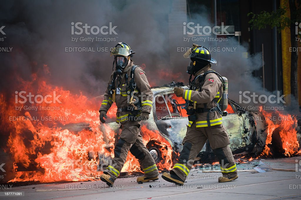 Fire fighters in front of a burning car stock photo