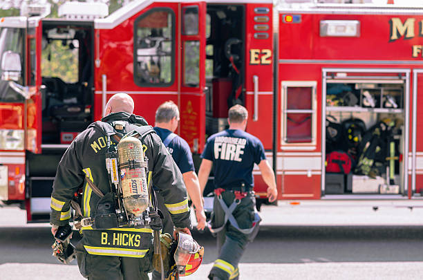 Fire Fighters Returning To Firetruck After Drill stock photo
