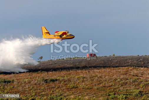 A twin-engined water bomber dumping its load on a forest fire