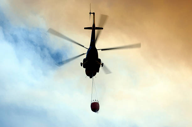 Fire fighting helicopter Image of a fire fighter helicopter, taken from below, with the smoke of the fire in the background. smoke jumper stock pictures, royalty-free photos & images