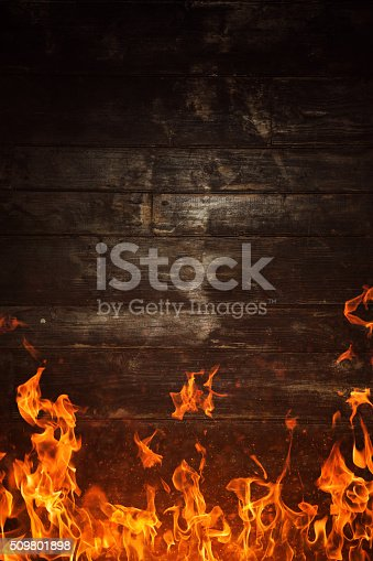 istock Fire flames and burnt wooden texture on background 509801898