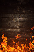 Fire flames and burnt wooden texture on background