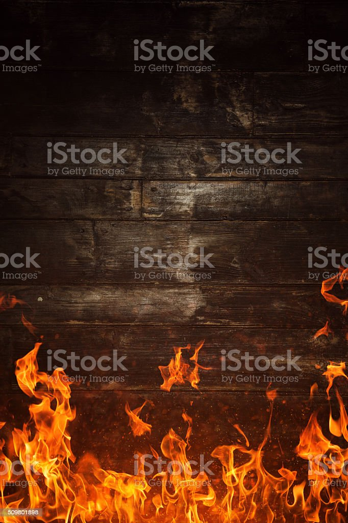 Fire flames and burnt wooden texture on background​​​ foto