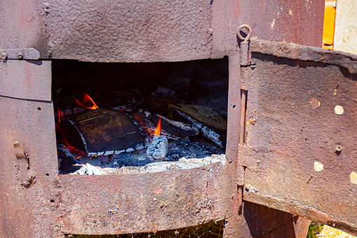 Fire flames are igniting and burning, blazing in the old rusty firebox.