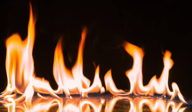 Fire Flames Igniting And Burning.Real fire , A line of real flames ignite on a black background. stock photo
