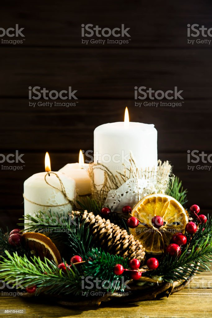fire from three white candles - a decorative Christmas composition with a wreath and tree branches. Hygge concept royalty-free stock photo