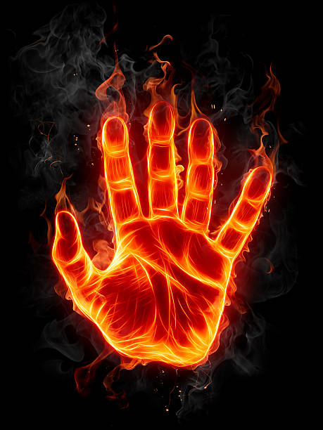 Fire hand burning against a black background stock photo