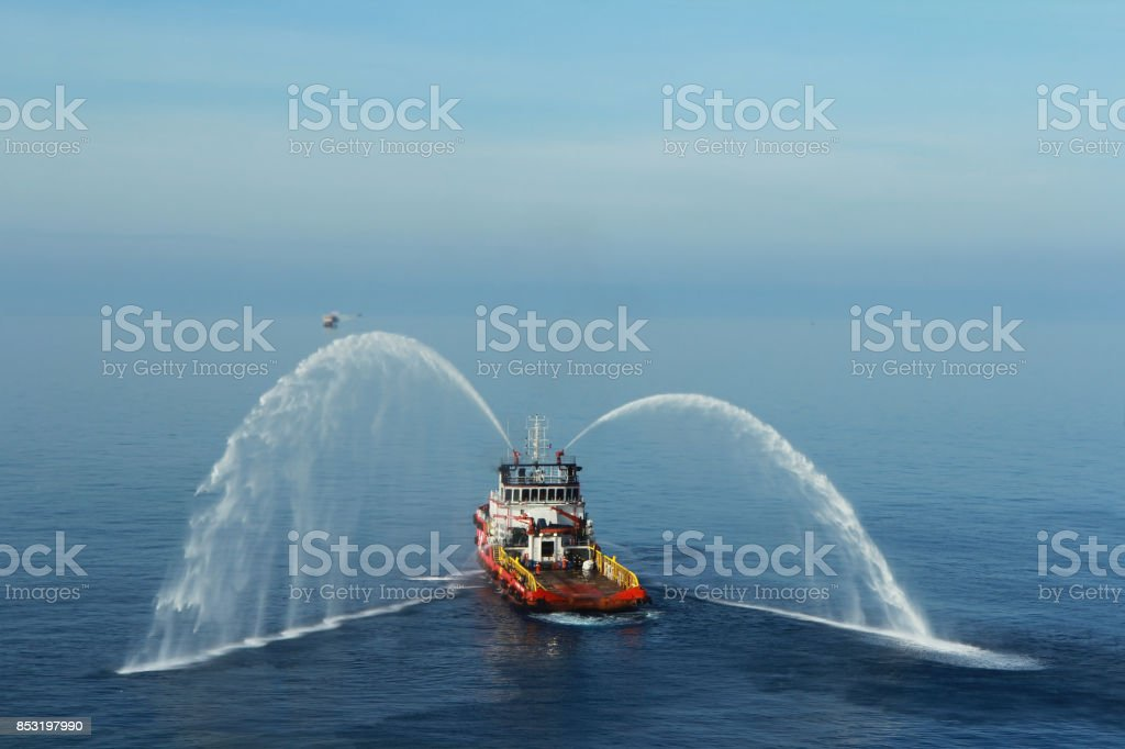 Fire hose boat is spraying water on the sea for supporting emergency case of fire of offshore oil and gas industry. Fire fighting boat sprays water on the sea. stock photo