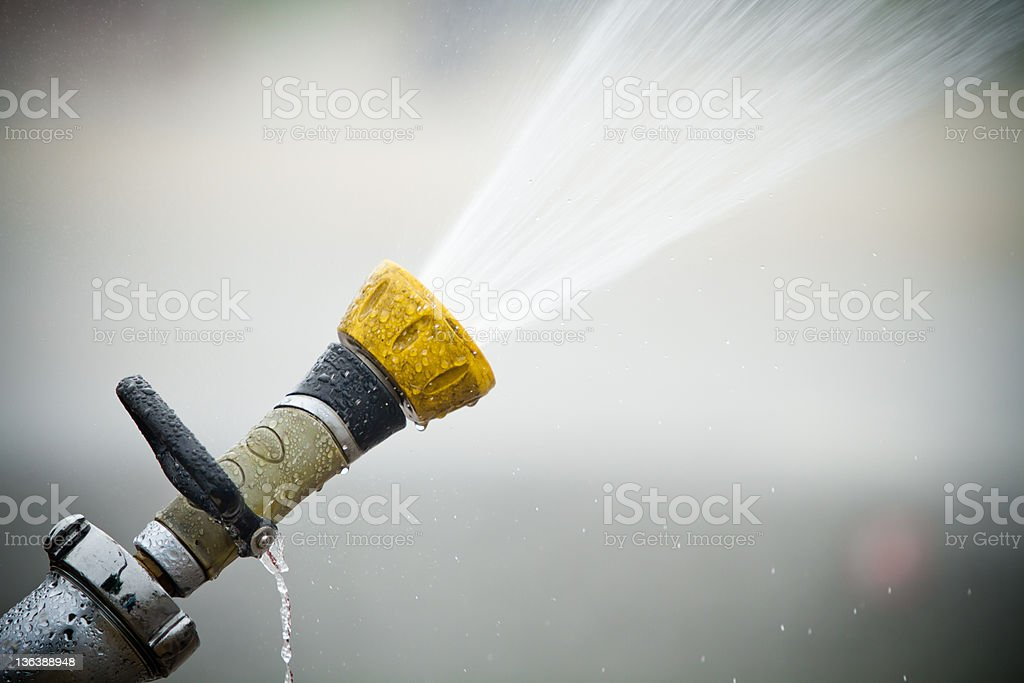 Fire hose shooting water out stock photo