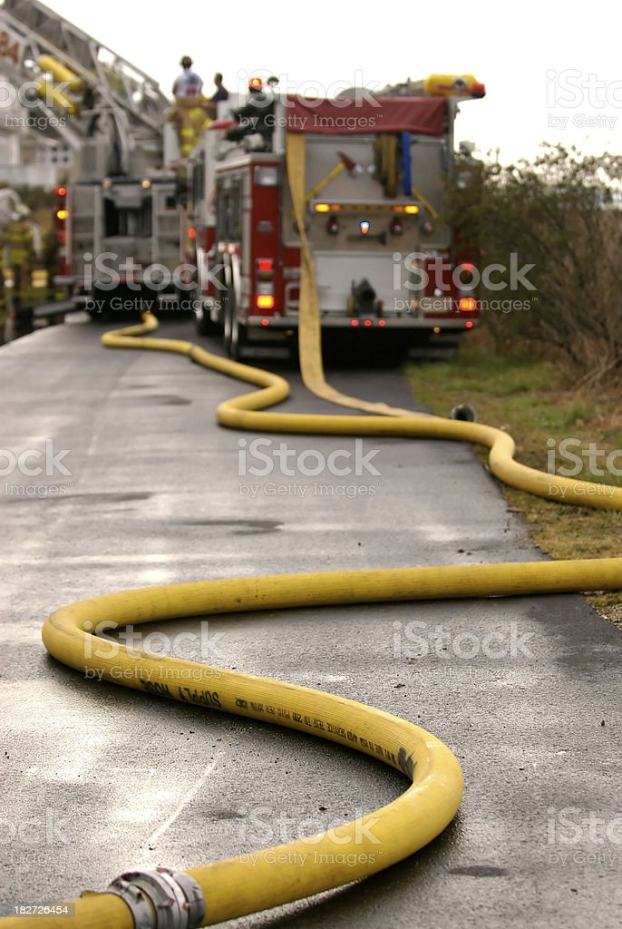 Fire hoses from hydrant to truck stock photo