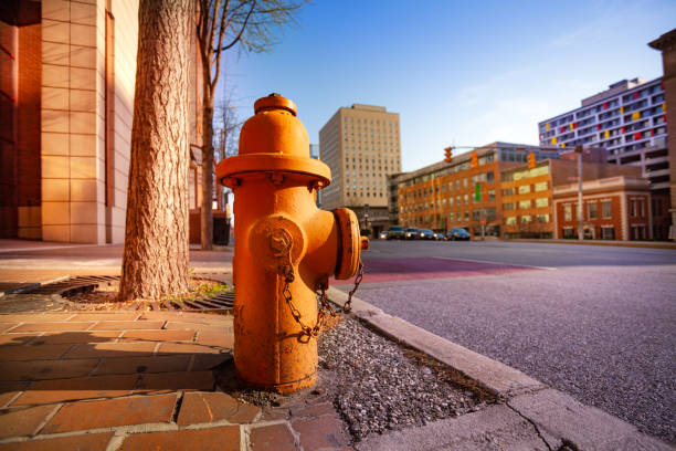 Fire hydrant on sidewalk of Baltimore city, USA Close-up picture of orange fire hydrant on the sidewalk of Baltimore city, Maryland, USA fire hydrant stock pictures, royalty-free photos & images