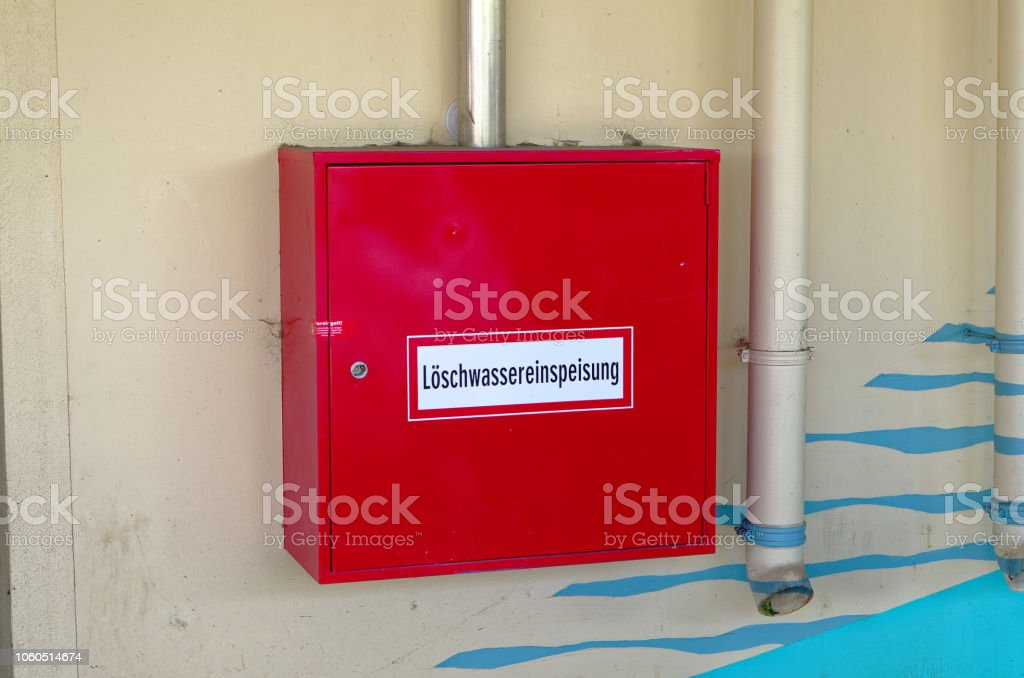 Fire hydrant with pipes on a wall in red with inscription in german...