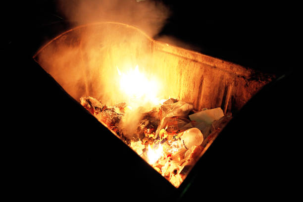 Fire in a dumpster Fire in a dumpster dumpster fire stock pictures, royalty-free photos & images